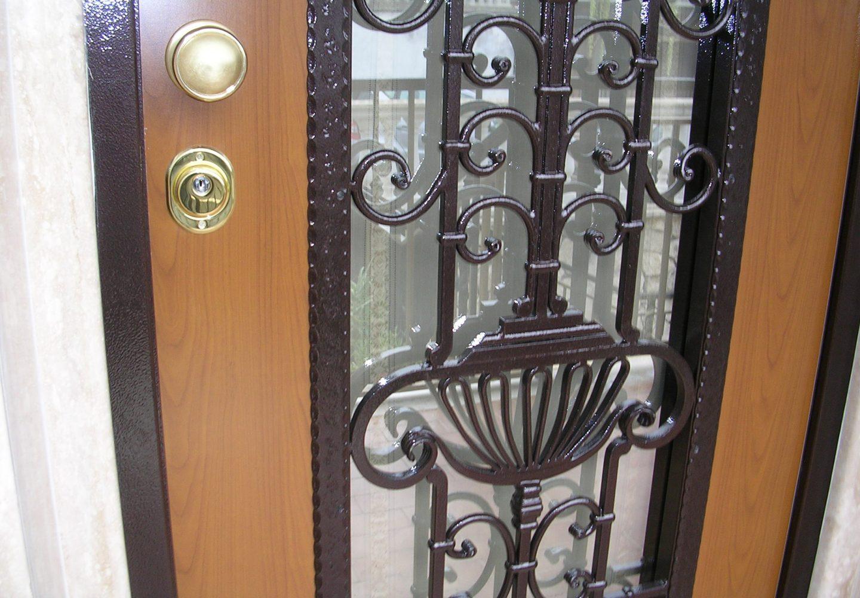 Dettaglio porta blindata con disegni in ferro e vetro