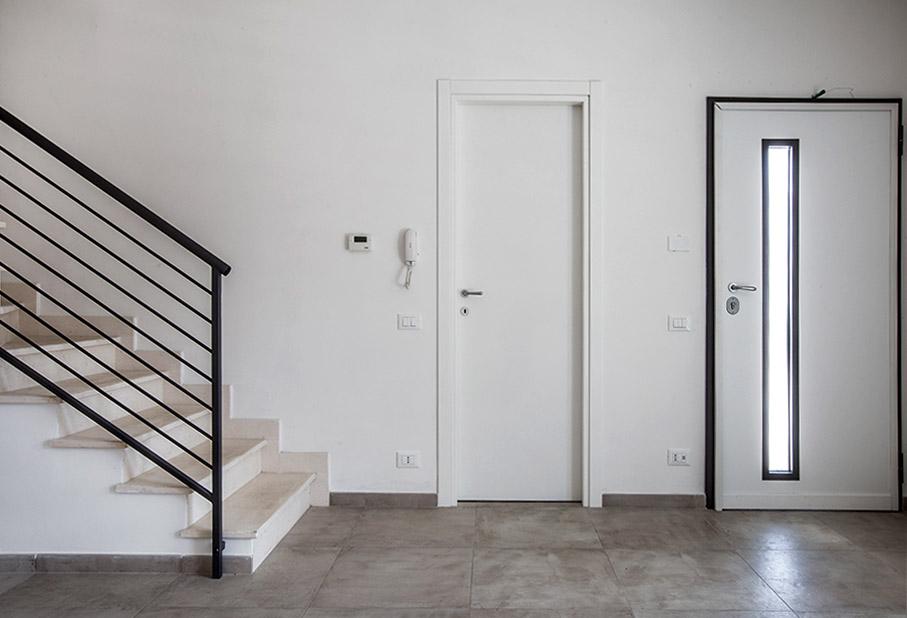 Interno con porta blindata bianca e vetro verticale